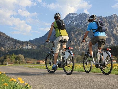 Radfahrer in Füssen vor den Alpen in Neuschwanstein