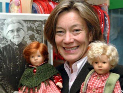 Die Geschaftsführerin der Kathe Kruse Puppen Andrea Kathrin Christenson steht mit zwei Puppen in der Fabrik in Donauwörth